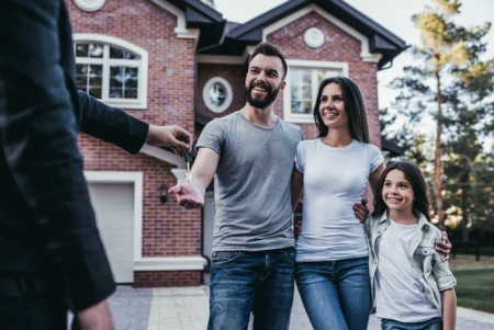 Smiling man, woman, and child accepting keys to new home from real estate agent