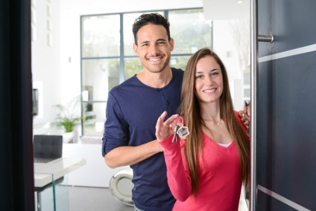 man and woman smiling and standing at a door holding house keys
